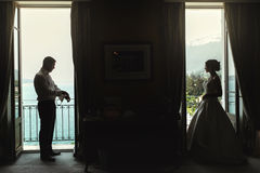 Beautiful bride and handsome groom separate on balcony at r Royalty Free Stock Photos