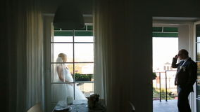 Beautiful sexy bride and handsome groom separate on balcony at the resort. Honeymoon concept stock video