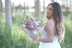 Beautiful bride with a perfect skin and amazing green . Young fashion bride with perfect skin and green eyes holding a wedding bouquet stock photos