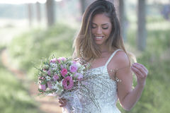 Beautiful bride with a perfect skin and amazing green . Young fashion bride with perfect skin and green eyes holding a wedding bouquet royalty free stock images