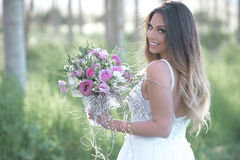 Beautiful bride in a stylish wedding dress smiling on a wedding day . Young fashion bride with perfect skin and green eyes holding a wedding bouquet royalty free stock photo