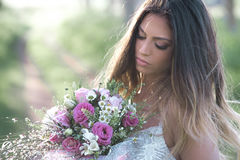Beautiful bride in a stylish wedding dress . Young fashion bride with perfect skin and green eyes holding a wedding bouquet royalty free stock photography