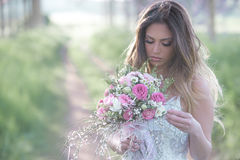 Beautiful bride in a stylish wedding dress . Young fashion bride with perfect skin and green eyes holding a wedding bouquet royalty free stock images