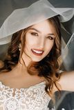 Beautiful sexy bride in white dress posing under curtain. Cheerful bride smiles bride putting earring behind the curtain Stock Images