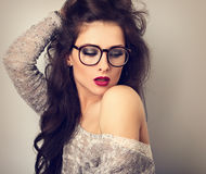 Beautiful bright red lips makeup woman in fashion glasses l. Ooking down and posing in grey blouse on blue background. CLoseup toned vintage portrait royalty free stock photo