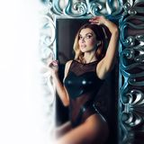 Beautiful sexy brunette with blue eyes. Portrait in the Studio, on the background of the mirror in beautiful frame. Beautiful sexy brunette with blue eyes Royalty Free Stock Photos