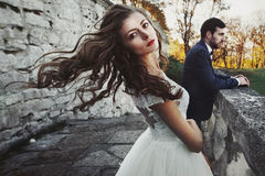 Beautiful sexy brunette bride waving her hair near her husband a Stock Images