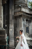 Beautiful sexy brunette bride in white dress walking up stairs,. Baroque church in Lviv background Royalty Free Stock Images