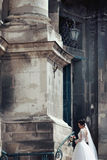 Beautiful sexy brunette bride in white dress walking up stairs,. Baroque church in Lviv background Stock Photography