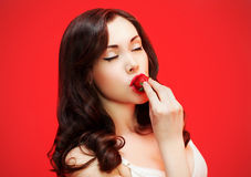 Beautiful brunette. Enjoying the taste of fresh strawberry royalty free stock photo