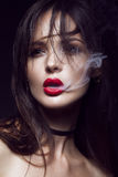 Beautiful sexy brunette girl with bright makeup, red lips, smoke from mouth. beauty face. Royalty Free Stock Photo