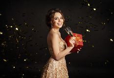 Beautiful sexy brunette girl holding a gift box and a glass of c. Hampagne and laughing. Black background, studio Stock Image