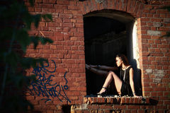 Beautiful sexy brunette girl posing in an old building collapsed Stock Photos