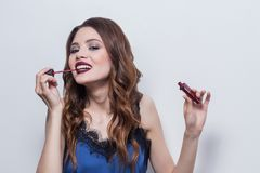 Beautiful brunette girl with professional make-up, in blue dress, with a big smile gets bright red lipstick and lip gloss on royalty free stock photo