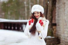 Beautiful sexy brunette girl with red lips in a fur vest and hat Royalty Free Stock Photos