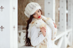 Beautiful sexy brunette girl with red lips in a fur vest and hat Stock Images