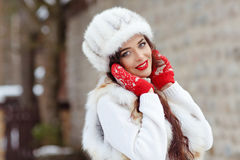 Beautiful sexy brunette girl with red lips in a fur vest and hat Stock Photos