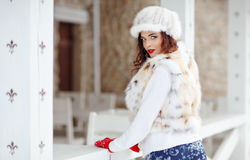 Beautiful sexy brunette girl with red lips in a fur vest and hat Stock Image