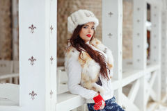 Beautiful sexy brunette girl with red lips in a fur vest and hat Royalty Free Stock Photo