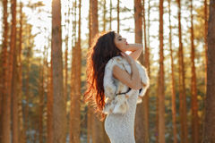 Beautiful sexy brunette girl with red lips in a fur vest and hat Royalty Free Stock Image