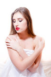 Beautiful sexy brunette girl with red lips touching herself naked shoulders wrapping in white cloth looking down on a white Stock Photo
