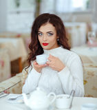 Beautiful sexy brunette girl with red lipstick in a white sweate. R, drinking tea at the table Royalty Free Stock Images