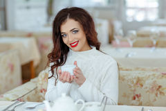 Beautiful sexy brunette girl with red lipstick in a white sweate. R, drinking tea at the table Stock Photography
