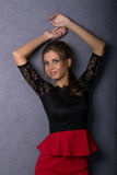Beautiful sexy brunette girl in red short skirt. Beautiful sexy brunette girl in the studio on a brown background in a red short skirt and stockings Royalty Free Stock Images