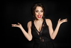 A beautiful sexy brunette girl is surprised and makes round eyes. Spreading her arms. Black background, studio Royalty Free Stock Image