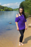 Beautiful brunette girl walking along a river in sunny summer day Stock Images