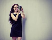 Beautiful sexy brunette with long hair with vintage camera in hand. Colorful hipster photo Royalty Free Stock Images