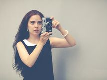 Beautiful sexy brunette with long hair with vintage camera in hand. Colorful hipster photo Royalty Free Stock Photography