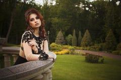Beautiful brunette luxury rich woman standing on a balcony