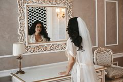 Beautiful and brunette model girl in fashionable peignoir looking in the mirror on her reflexion at classic. Interior stock photo