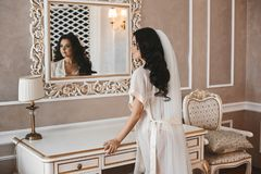 Beautiful and brunette model girl in fashionable peignoir looking in the mirror on her reflexion at classic. Interior royalty free stock image