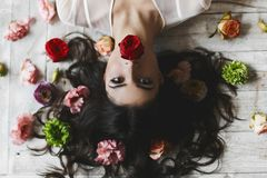 Beautiful sexy brunette model lies on the floor with disheveled hair among flowers - view from above, upside down.  Royalty Free Stock Photos