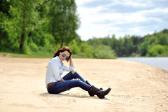 Beautiful sexy brunette sitting on a beach Royalty Free Stock Images