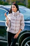 Beautiful brunette in sunglasses and a fur coat walks down the street on sunny day and looks away. Late autumn or early winte royalty free stock photography