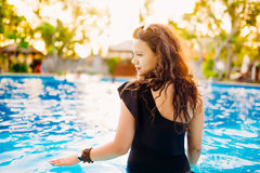 Beautiful and brunette with swimwear sitting by the pool and enjoying summer. Royalty Free Stock Photo