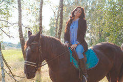 Beautiful sexy brunette wearing jeans, blouse and black jacket riding a horse at sunny summer day Royalty Free Stock Image