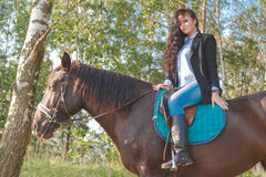 Beautiful sexy brunette wearing jeans, blouse and black jacket riding a horse at sunny summer day. Stock Photo