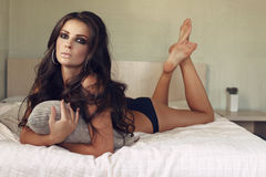 Beautiful sexy brunette woman in black lingerie relaxing on the bed Stock Images