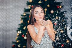 Beautiful brunette Christmas woman blowing snow with her hands and looking at the camera. A young girl wears a silver dress stock photo