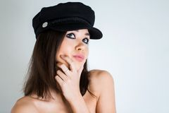 Beautiful sexy brunette woman with bright makeup and a black cap on a white background looking up. She thought, dreaming about som. Ething, plans. Close up Stock Photos
