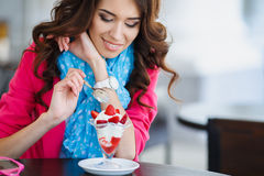 Beautiful Sexy brunette woman in Cafe. Beautiful sexy brunette woman in restaurant cafe with ice cream cake alluring woman in bright clothes and hairstyle and Royalty Free Stock Photography