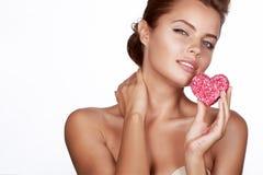 Beautiful brunette woman eating cake shape of heart romanti royalty free stock photos