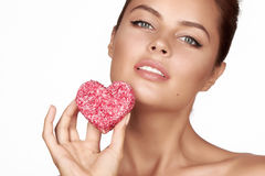 Beautiful sexy brunette woman eating cake shape of heart on a white background, healthy food, tasty, organic, romantic valentine d Stock Photos