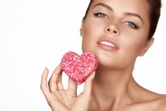 Beautiful brunette woman eating cake shape of heart on a white background, healthy food, tasty, organic, romantic valentine d. Ay royalty free stock photos