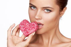 Beautiful brunette woman eating cake shape of heart on a white background, healthy food, tasty, organic, romantic valentine d Stock Image