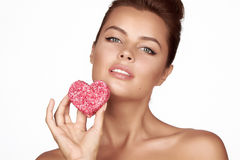 Beautiful brunette woman eating cake shape of heart on a white background, healthy food, tasty, organic, romantic valentine d. Ay royalty free stock photography